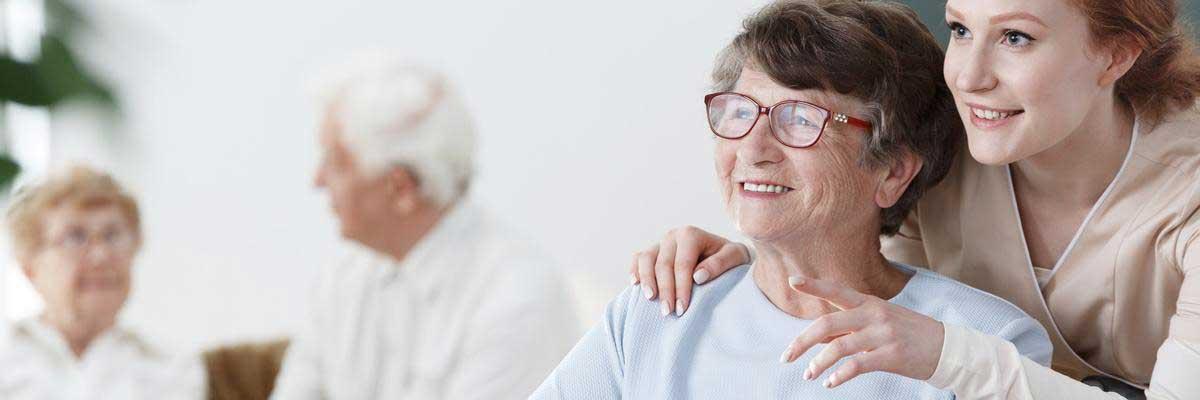 Eine Altenpflegerin kümmert sich um eine ältere Heimbewohnerin